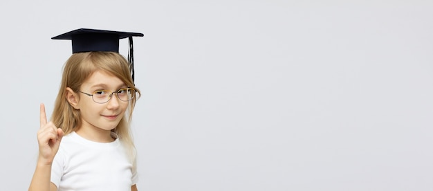 Concetto di infanzia, scuola, istruzione, apprendimento e persone - ragazza felice con gli occhiali in cappello da scapolo o sparviere su sfondo bianco