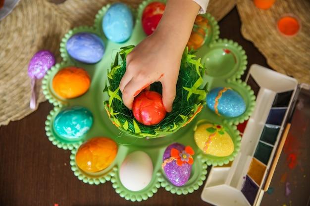 Mano infantile depone un uovo rosso dipinto per pasqua su un vassoio di plastica verde in piedi su un tavolo di legno. vista dall'alto
