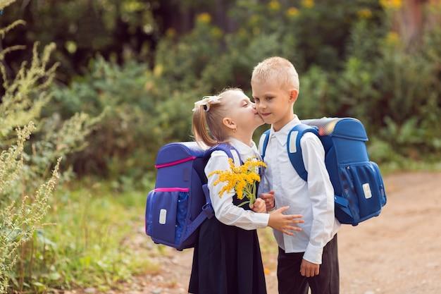Bambini 7-8 anni, studenti delle scuole elementari con zaini e uniformi scolastiche, una ragazza bacia un ragazzo sulla guancia