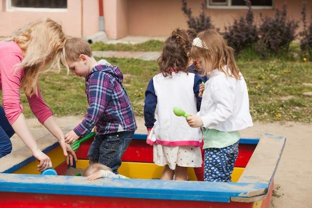 I bambini stanno giocando al parco giochi con la sabbia nella sabbiera