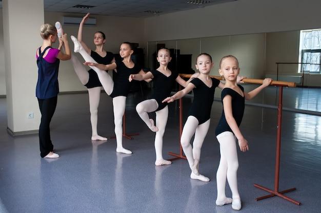 Ai bambini vengono insegnate le posizioni di balletto nella coreografia.