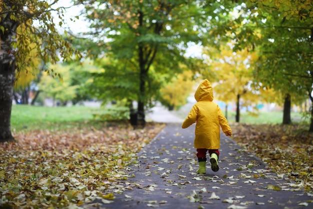 I bambini nel parco autunnale camminano con gli impermeabili durante il giorno