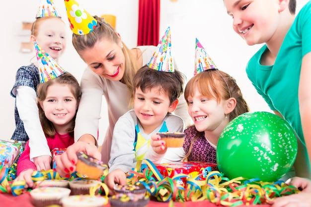 I bambini alla festa di compleanno afferrano muffin e torta, i bambini indossano cappelli, palloncini e stelle filanti di carta per la decorazione