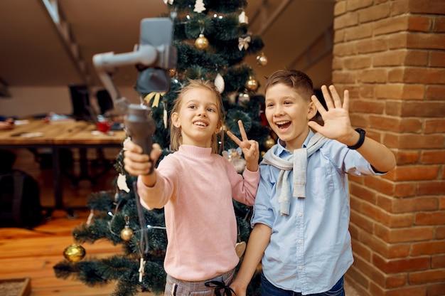 I blogger per bambini fanno selfie all'albero di natale