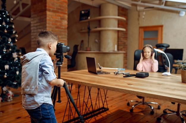 Blogger di bambini che sparano sulla macchina fotografica per il blog. blogging per bambini in home studio, social media per un pubblico giovane, trasmissione internet online