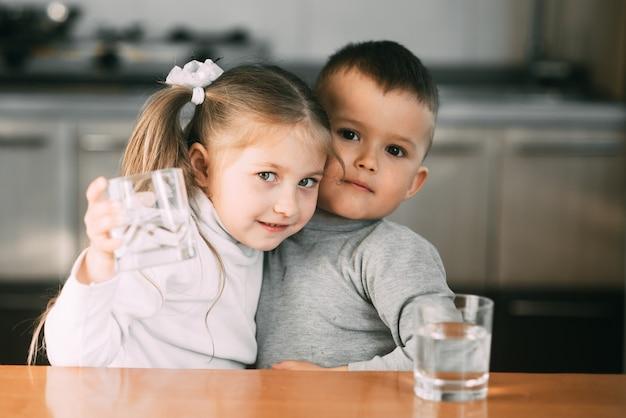 Bambini ragazzo e ragazza in cucina a bere acqua da bicchieri, abbracciando e sorridendo molto dolce