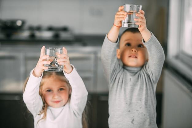 Bambini ragazzo e ragazza in cucina con bicchieri sollevati sopra la sua testa molto dolci