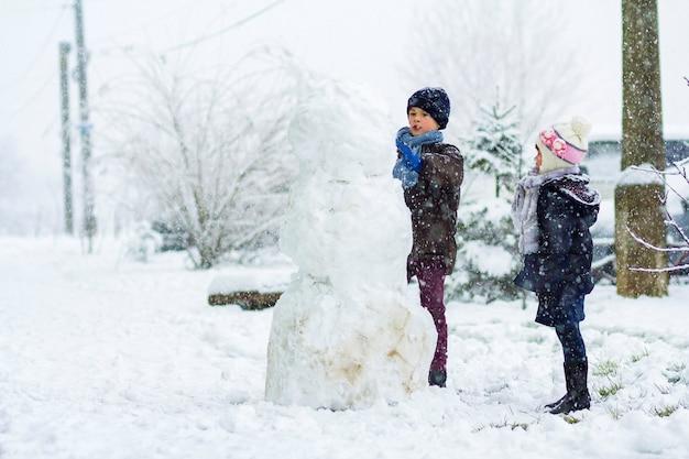 Bambini ragazzo e ragazza all'aperto in inverno nevoso stanno facendo un grande pupazzo di neve