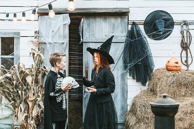 Bambini un ragazzo in costume da scheletro e una ragazza in costume da strega che si divertono a una festa di halloween sotto il portico decorato decorated