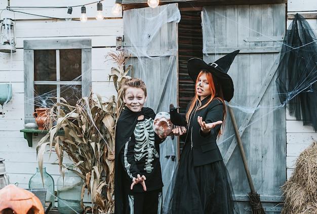 Bambini un ragazzo in costume da scheletro e una ragazza in costume da strega che si divertono a una festa di halloween halloween