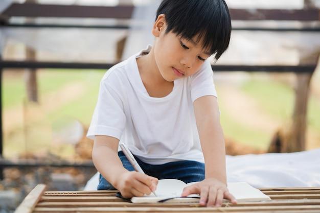 Ragazzo dei bambini che scrive su carta per fare i compiti a scuola