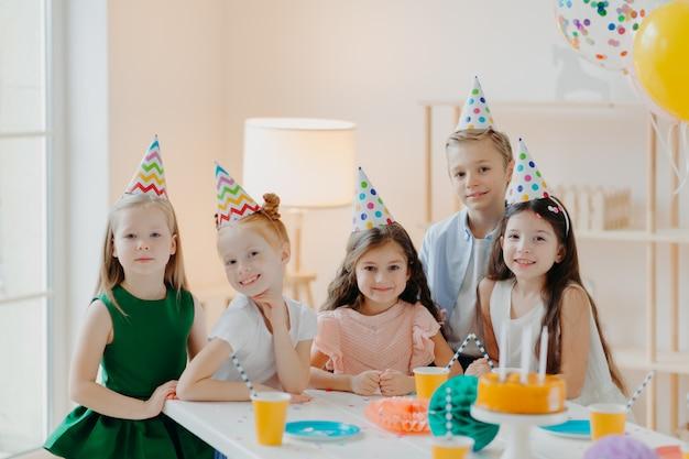 Concetto di bambini, celebrazione e compleanno. i bambini positivi si divertono insieme alla festa, indossano cappelli a cono