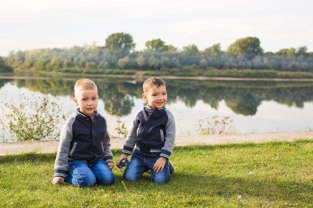 Bambini, infanzia, concetto di persone - ragazzi che giocano su una spiaggia vicino al fiume.