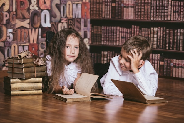 Bambini bambini che leggono libri in biblioteca con interesse