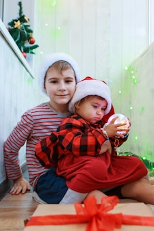 Bambini in costumi natalizi con un giocattolo dell'albero di natale.