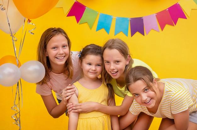 I bambini si congratulano con la festeggiata a una festa su uno sfondo giallo