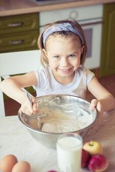 Bambini che cucinano felicità kid home concept. la ragazza mescola la pasta