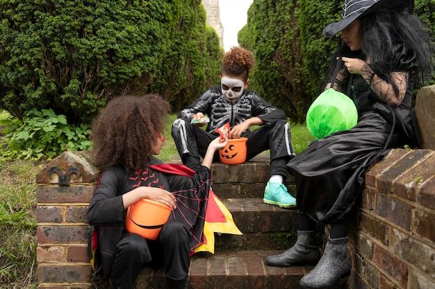 Bambini in costume che mangiano le loro caramelle