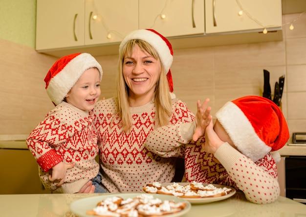 I bambini decorano i biscotti di natale con la glassa di zucchero. ragazzi carino bambino caucasico decorare i biscotti di pan di zenzero con divertimento.