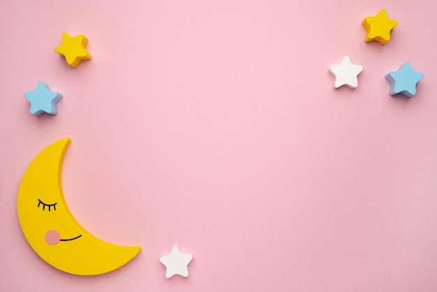 Giocattolo evolutivo per bambini per lo sviluppo delle capacità motorie, una falce di luna con bilanciatore di stelle, su uno sfondo rosa vista dall'alto