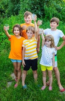 I bambini bevono acqua fuori insieme.