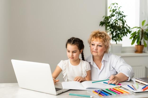 Bambini e istruzione, insegnante o nonna che insegna con il taccuino da internet alla ragazza.