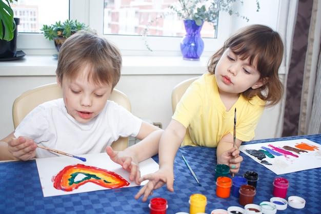 Bambini impegnati nella creatività all'interno della casa. il bambino disegna e colora l'immagine con colori e un pennello.