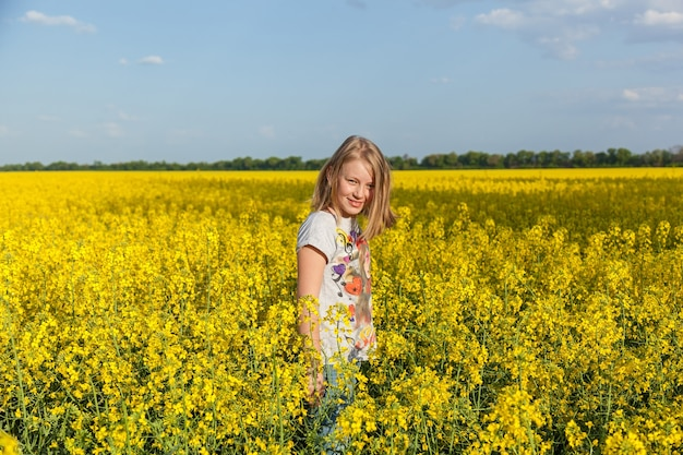 Bambini nel campo con i fiori gialli dello stupro in fiore