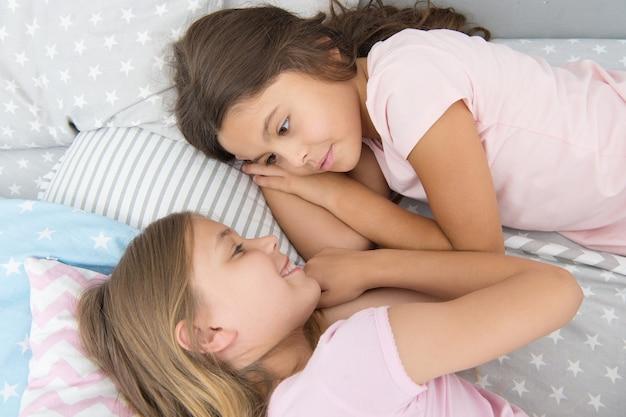 Amici dei bambini. i bambini carini e affascinanti hanno del tempo libero prima di dormire. dialogo migliori amici. concetto di sorellanza. condivisione di segreti. bambini che si rilassano a letto. sorelle che preparano il sonno. bella serata. migliori amici.