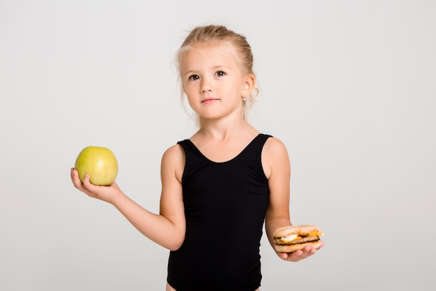 La ragazza dei bambini che sorride tiene una mela e un hamburger. scegliere cibi sani, niente fast food