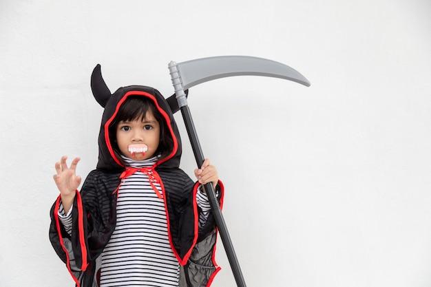 Ragazza dei bambini che indossa un misterioso vestito di halloween che tiene una falce su sfondo bianco