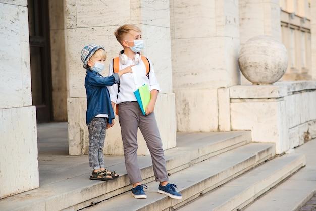 Bambini che tornano a casa dopo la scuola. bambini che indossano una maschera medica che camminano per strada. epidemia di coronavirus. la vita reale durante l'epidemia di coronavirus.