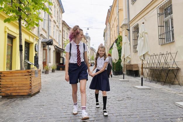Bambini che vanno a scuola, due sorelle ragazze che camminano insieme, tenendosi per mano