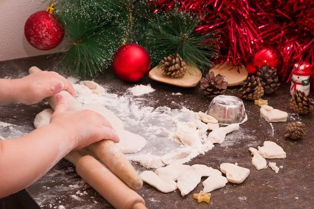 Le mani dei bambini tirano l'impasto per i biscotti di natale, lo sfondo del nuovo anno, lo spazio della copia