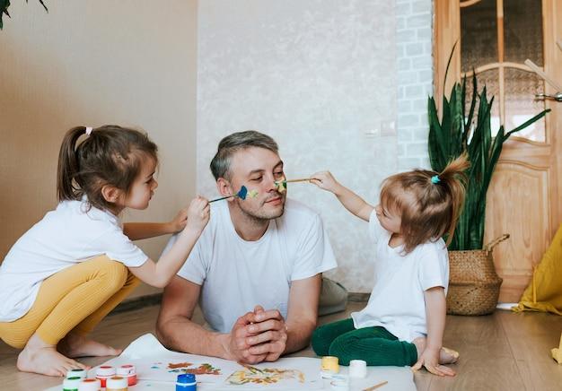 I bambini si divertono con il padre, le ragazze disegnano sulla pelle del viso di un uomo con pitture colorate creatività e immaginazione festa del papà e il concetto di famiglia
