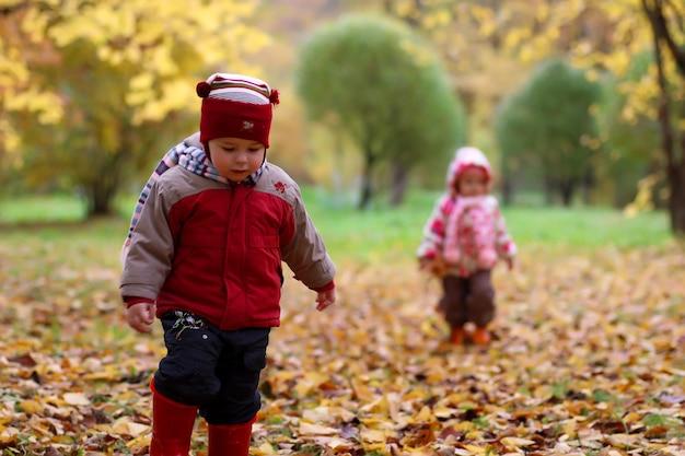 I bambini si divertono durante una passeggiata nel parco autunnale