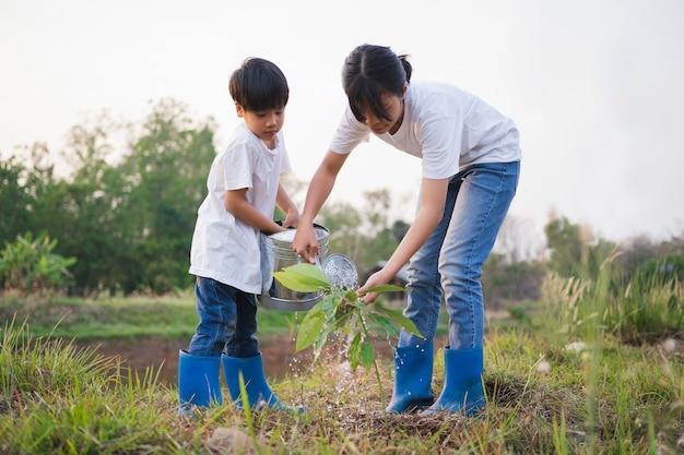 Bambini che aiutano a piantare alberi in giardino per salvare il mondo. concetto di ambiente eco