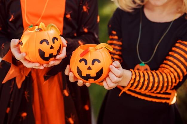 I bambini tengono due zucche jackolanterns con dolci i bambini indossano costumi di halloween