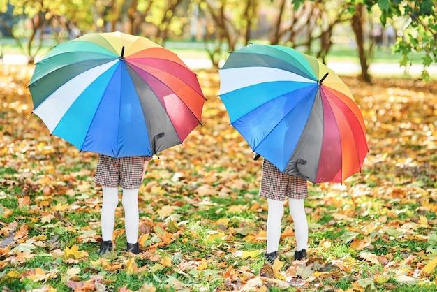 Bambini che tengono un ombrello colorato nella foresta autunnale