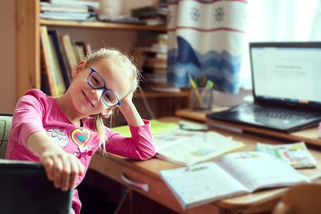 Bambini homeschooling, felice bambina seduta al tavolo con laptop e libri scolastici