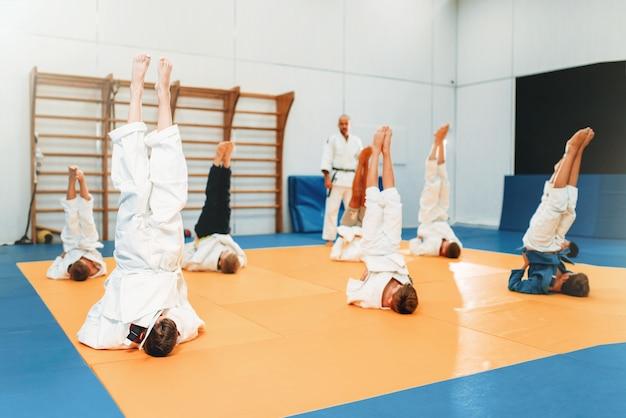 I bambini karate, i bambini in kimono praticano l'arte marziale nella hall. ragazzini e ragazze in uniforme sulla formazione sportiva, esercizio a testa in giù