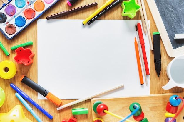 Concetto di bambini o ragazzi. giocare a giocattoli e disegnare materiali sul tavolo. vista dall'alto.