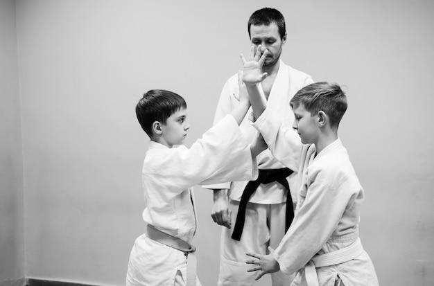 I bambini in kimono iniziano ad allenarsi sull'aikido.