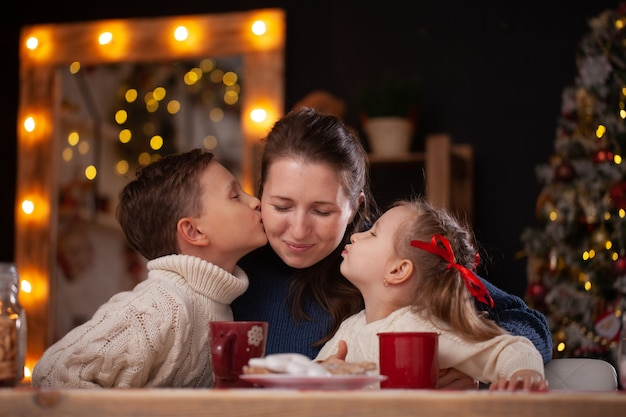 Bambini che baciano la madre in una cucina decorata a natale