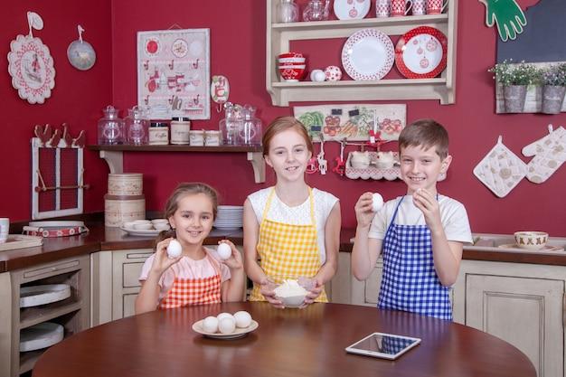 Bambini in cucina che cercano di imparare a cucinare. migliori amici in grembiule che tengono la pasta in mano e fanno la torta in cucina e si guardano. colpo dello studio.