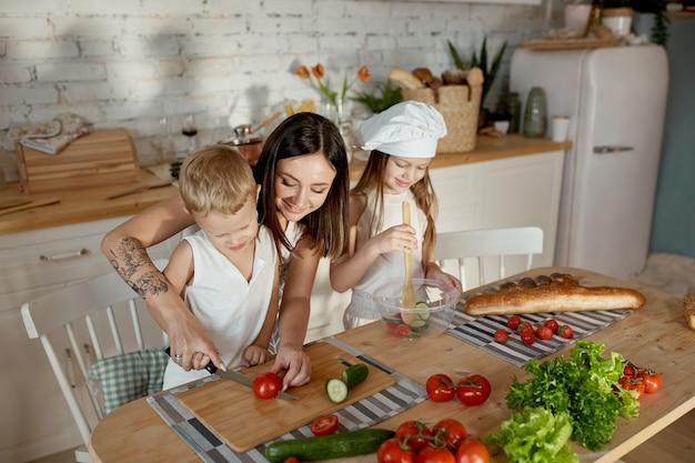 I bambini imparano a preparare un'insalata in cucina. giornata libera in famiglia, pranzo con le tue mani. mamma e giovani cuochi