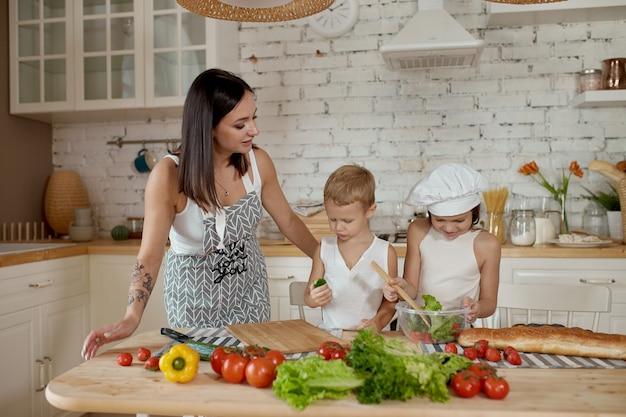 I bambini imparano a preparare l'insalata vegana in cucina. giornata libera in famiglia, pranzo con le tue mani. mamma e giovani cucinano cibi vegani