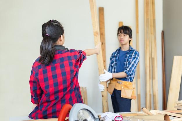 Bambini che imparano la lavorazione del legno nel laboratorio artigianale, ragazzo adolescente con la sua sorellina che costruisce un laboratorio insieme in un laboratorio di falegnameria.