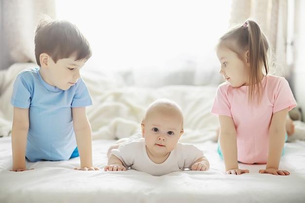 I bambini si trovano sul letto accanto al neonato, sorellina. emozioni dei bambini.