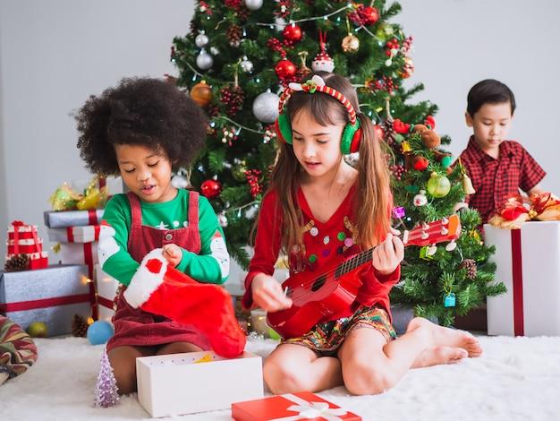 I bambini di molte nazionalità festeggiano il giorno di natale, i bambini sotto l'albero di natale suonano la chitarra